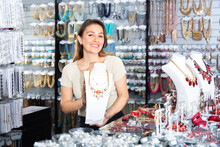 Young Smiling Hispanic Salesgirl Offering Stylish Adornments In Costume Jewelry Store, Showing Elegant Necklace On Mannequin .