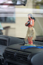 A Figurine Of A Hawaiian Girl With A Guitar On The Car Panel.