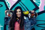 Fototapeta Młodzieżowe - Girl with skateboard graffiti wall background