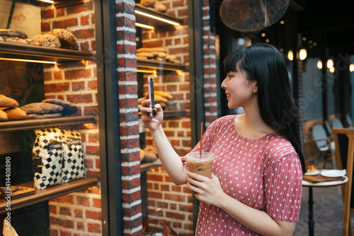 Obraz Beautiful asian thai long dark hair woman taking picture of bread inside bakery shop from window street outdoor. - fototapety do salonu