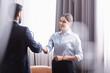 Smiling businessman handshaking with arabian partner in restaurant