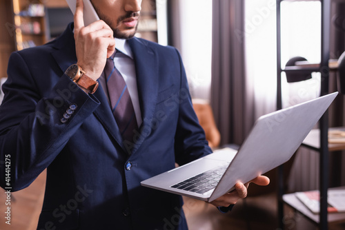 Cropped view of young businessman talking on smartphone and holding laptop in restaurant