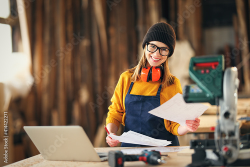 Smiling craftswoman working with laptop and papers in joinery workshop #414422271