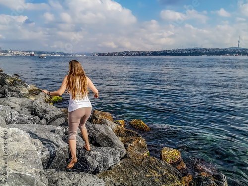 Slika na platnu Young slender woman runs on huge stones on Bosphorus embankment on the backdrop of Istanbul panorama (Turkey) - a view from the back
