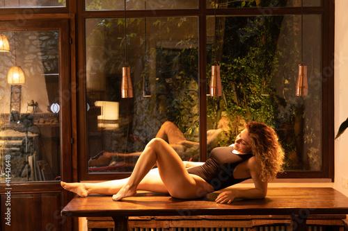 Obraz bella ragazza posa seminuda sul tavolo della sala da pranzo, donna oggetto - fototapety do salonu