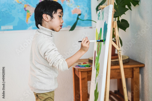 Boy child painting at home - Focus on face Fototapeta