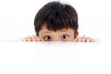 Portrait Of An Asian Boy Peeking Through The Surface Of Table Isolated On White Background.