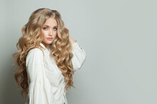 Perfect Young Woman With Long Blonde Healthy Curly Hairdo On White Background