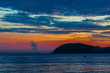 Sunset On The Island. Sea Clouds And A Hill.