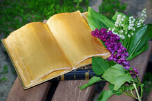 An Open Book On A Garden Bench And A Bouquet Of Lilies Of The Valley And Lilacs.