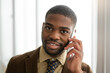 handsome young african man with mobile phone in suit at office