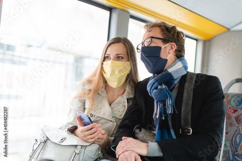 Obraz Couple in public transport bus wearing masks - fototapety do salonu