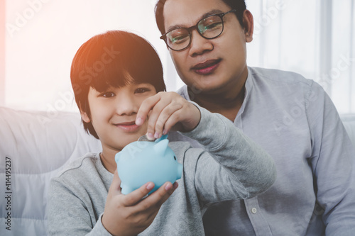 Stampa su Tela Asian Father is teaching his son in money saving by inserting coin into a blue piggy bank for Financial Education concept