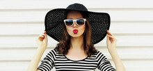 Portrait Of Beautiful Young Woman Blowing Her Red Lips Sending Sweet Air Kiss Wearing A Black Round Summer Straw Hat On A White Background