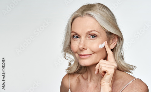 Fotografia Smiling 50s middle aged mature older woman applying facial cream on face looking at camera isolated on white background