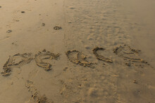 Panoramic Landscape View Of 'Peace' Word Written Or Made In Yellow Sand On A Sandy Beach In India