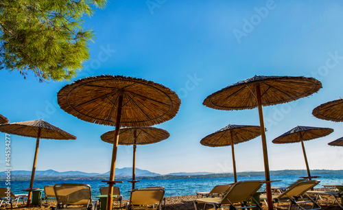 Fotografie, Obraz sunshade awnings  and beach loungers on the amazing  beach  on idyllic greek isl