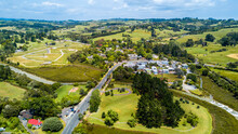 Aerial View Of A Little Village In The Middle Of The Countryside Spotted With Farms And Forest. Auckland, New Zealand.