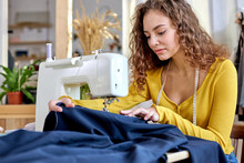 Young Tailor Working On Sewing Machine, Hand Making Clothes In Home Interior. Caucasian Curly Female Sits Enjoying Process Of Sewing Clothes. Creative Skills Design, Hobbies And Lifestyle Concept