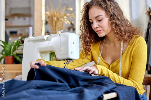 Fotografia, Obraz young tailor working on sewing machine, hand making clothes in home interior