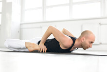 Man Working Out, Doing Frog Yin Yoga Pose, Mandukasana Posture In Class On Fitness Mat. Sport, Stretching, Yoga Concept