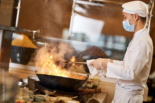 Fototapeta Professional Asian chef making stir-fry in flaming wok obraz