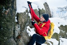 Handsome Climber In A Red Down Jacket And Yellow Backpack Climbs Rocks With An Ice Ax. Mountain Climbing.