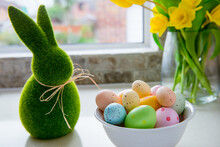 White Bowl With Colored Easter Eggs, Bouquet Of Yellow Tulips And Daffodils Flowers And Green Bunny Rabbit On White Kitchen Table Near Window. Festive Ester Spring Card. Selective Focus. Copy Space.