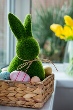 Close Up Easter Bunny Rabbit In Straw Basket With Colored Eggs On The Windowsill With Fresh Spring Tulips And Daffodils Flowers Bouquet On The Background. Happy Easter Vertical Card. Selective Focus.