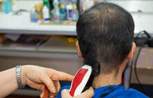 Close-up Of Hairdresser Using Electric Hair Clipper For Cut Human Head Hair In Barber Shop. Conceptual Of Barber Serving Hair Cut Service To Customer.