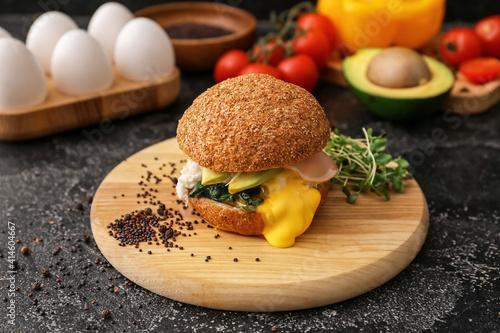 Fotografie, Tablou Tasty burger with florentine egg and fresh vegetables on dark background, closeu