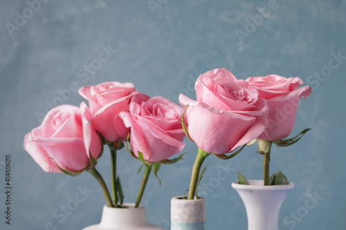Beautiful pink roses in vases on color background Fototapeta