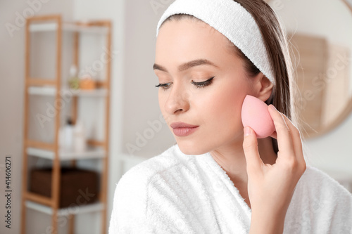 Obraz na plátně Beautiful young woman with sponge applying makeup at home