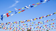 Multi Colored Party Rainbow Flags On Blue Sky For Celebration. Flags Colors Blue Sky