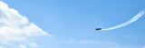 airplane doing acrobatics in blue sky leaves a smoke. Blue sky with airport contrail clouds.