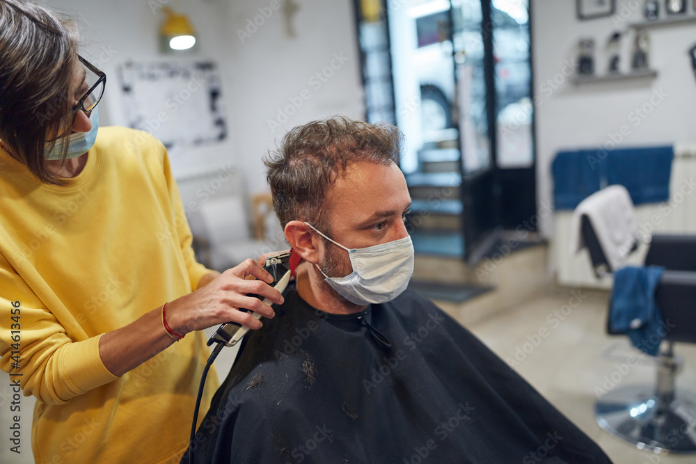 Fototapeta Hairdresser and customer in a salon with medical masks during virus pandemic. Working with safety mask.