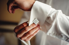 A Successful Man Wears Silver Cufflinks On The Cuff Of A White Shirt. The Hands Of The Bridegroom Fix A Cufflinks On The Sleeve Of A White Shirt. Close-up Men's Accessories. Morning Of The Groom
