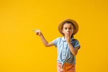Shocked Kid In Straw Hat Covering Mouth And Pointing With Finger Isolated On Yellow