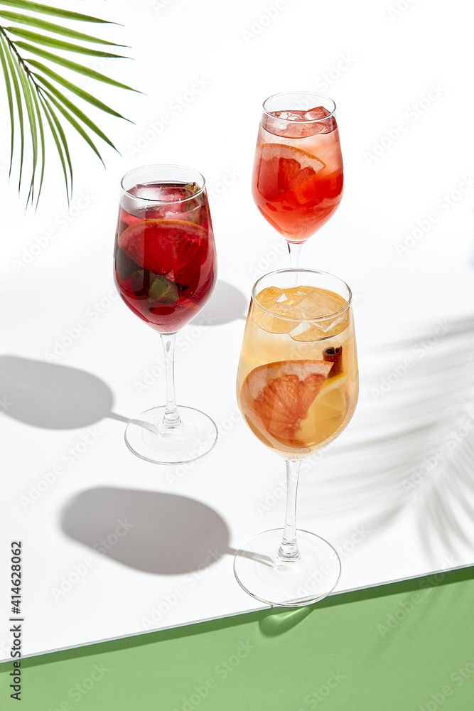 Fototapeta Assortment of sangria drinks on white table. Sunshine with hard shadow. Palm leaves and shadow. Fresh, summer, tropic, beach drink concept