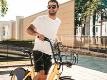 Portrait Of Handsome Smiling Stylish Hipster Lambersexual Model.Man Dressed In White T-shirt. Fashion Male Riding A Bike On The Street Background In Sunglasses