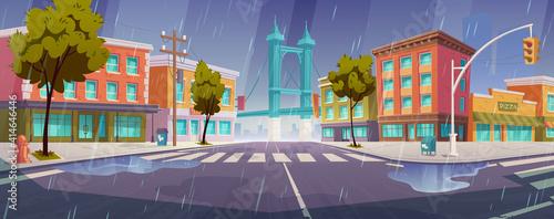 Fotografija Rain on city street with houses, road with pedestrian crosswalk and traffic lights