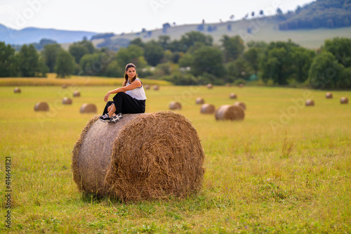 Fototapeta Young woman at the country side on a haystack