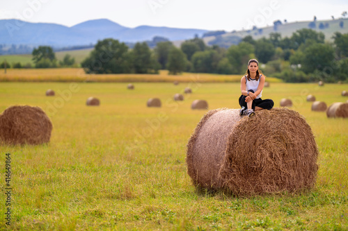 Obraz na plátně Young woman at the country side on a haystack