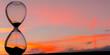 Leinwandbild Motiv Time passing at sunset with hourglass
