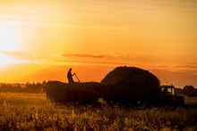 Silhouette Of A Man Folding Hay Into A Tractor In A Field At Sunset. Rural Lifestyle. Ukraine. Making Hay For Cattle.