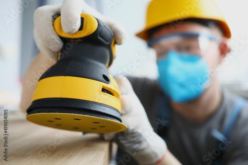 Fototapeta Master builder in protective mask is holding disc sander. Renovation services concept obraz