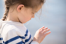 Beautiful Little Girl Watching On A Small Ladybug On Her Hand Against River Surface.
