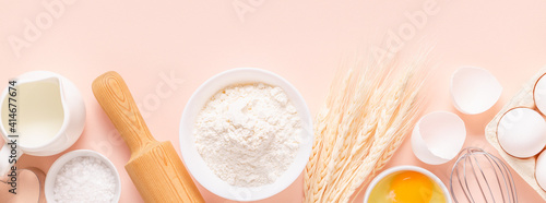 Photo Ingredients for baking on light pink background.