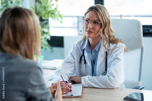 Beautiful mature female doctor talking while explaining medical treatment to patient in the consultation Fototapete