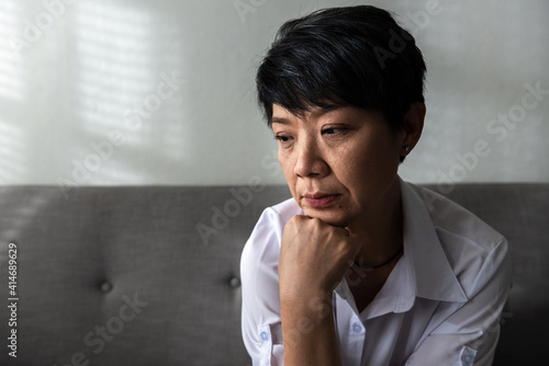Canvas Print Close-up Senior Asian woman sitting on a couch at her home, an unhappy elder wom